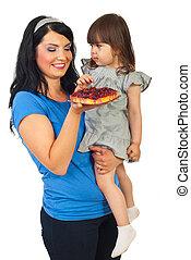 Mother giving tart fruit to daughter