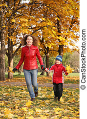 mother goes for a walk with the son in the park in autumn