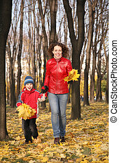 mother goes for a walk with the son in the park in autumn with yellow leaves