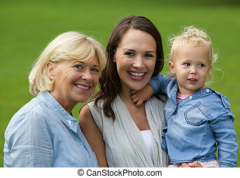 Mother grandmother and baby daughter smiling