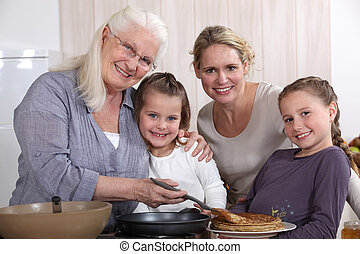 Mother, grandmother, and girls cooking pancakes