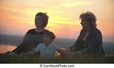 Mother, grandmother with little son sitting on the grass swatting at mosquitoes and talking at sunset