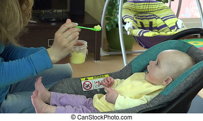 mother hand feeding hungry infant baby with mash in spoon. 4K