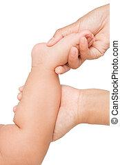 Mother hand massaging foot of her baby