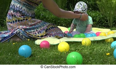 Mother hands put cap on unhappy baby daughter head in...