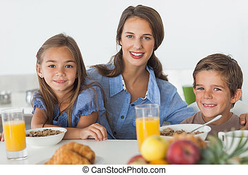 Mother having breakfast with her children