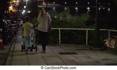 Mother having evening walk with elder son and baby