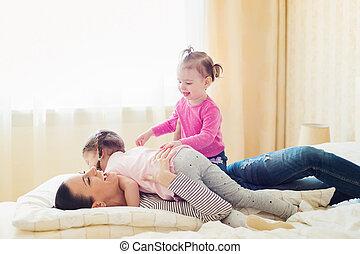 Mother having fun with her daughters in her bedroom - ...