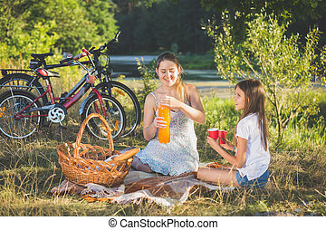 Mother having picnic by the river with daughter. Mother pouring orange juice in daughter's cup