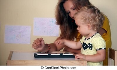 mother help her baby girl using tablet computer sitting at table.