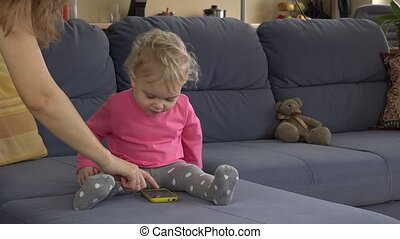 Mother help her lovely baby daughter to use smart phone sitting on sofa.