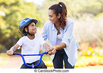 mother help her son ride a bicycle - loving mother help her...