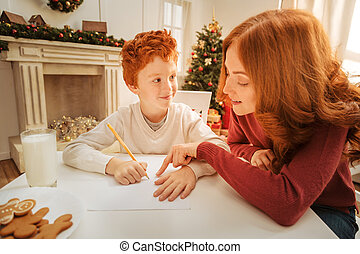 Mother helping adorable son with letter to santa claus