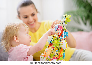 Mother helping baby made Easter decoration