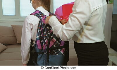 Mother Helping daughter To Pack Bag Ready For School. First Day Of School concept