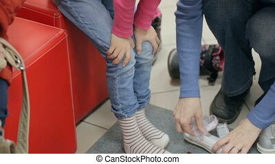 Mother helping daughter to try on shoes