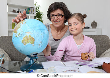 Mother helping daughter with geography homework
