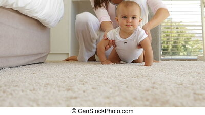 Mother helping her baby girl crawl away on the rug at home ...