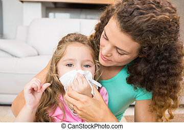 Mother helping her daughter blow her nose