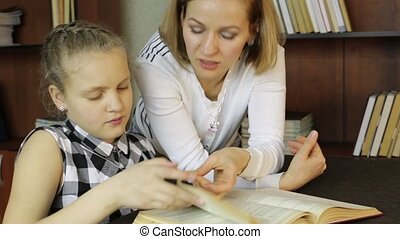 mother helping her daughter do homework. Girl makes lessons, reading
