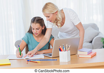 Mother helping her daughter to do her homework