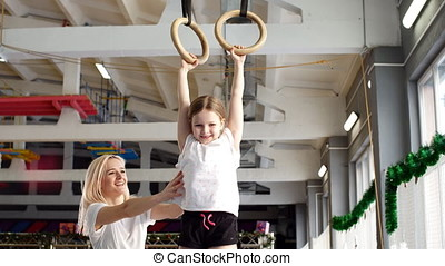 Mother helping her daughter to play sports on gymnastic rings.