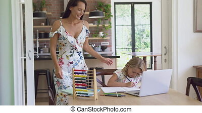Mother helping her daughter with homework in a comfortable ...