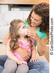 Mother helping her little daughter blow her nose