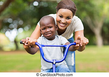 mother helping her son ride a bicycle