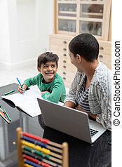 Mother helping his son with his homework on a table