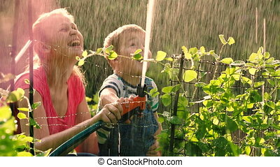 Mother helping son to water the garden with hose