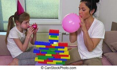 Mother helps daughter blow balloons