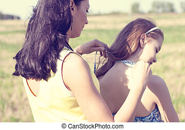 Mother helps daughter to braid hair in summer, family vacation girl woman assistance concept idea