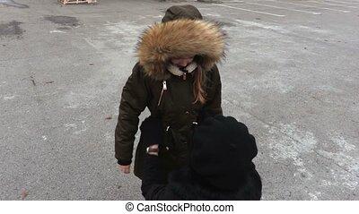Mother helps her daughter arrange a jacket hood