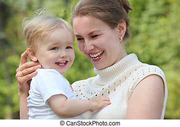 Mother hold baby on hands outdoor in summer and looks on he
