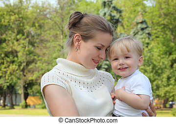 Mother hold baby on hands outdoor in summer