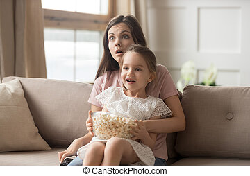 Mother hold daughter on lap watching movie feels shocked