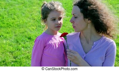 Mother hold red flower and tell about WWII to her little ...