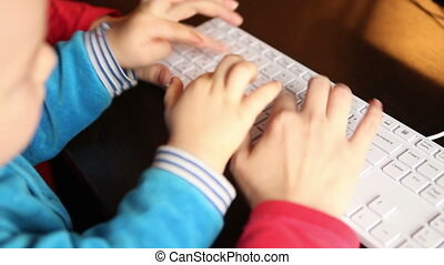 mother holding a child is typing on the keyboard
