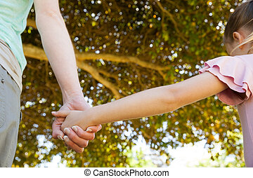 Mother holding a hand of her daughter outdoors