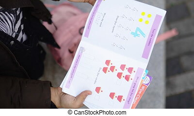 Mother holding and leafing through colorful kindergarten books about shapes, numbers, and letters. Woman looking at books for young children from above. Kindergarten literature
