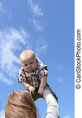 mother holding baby boy against blue sky