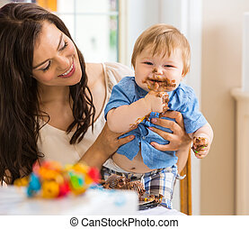 Mother Holding Baby Boy Eating Cake With Icing On Face