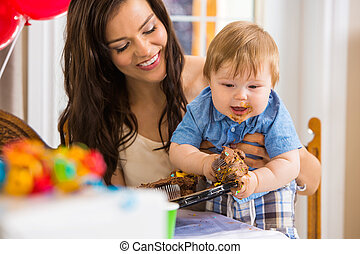 Mother Holding Baby Boy Eating Cupcake
