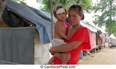 Mother holding baby in shanty