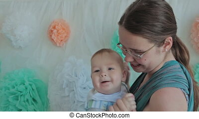 Mother holding baby in sling, baby boy laughing and smiling