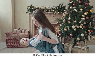 Mother holding baby in sling near christmas tree