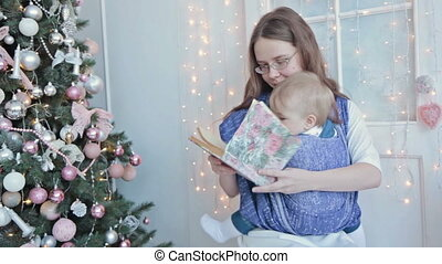 Mother holding baby in sling - Mother holding baby and...