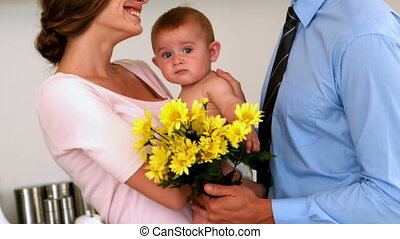 Mother holding baby with father holding flowers