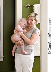 Mother holding bare baby in bathroom, ready to take a bath